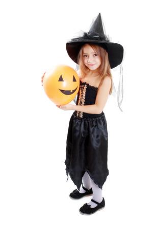 Happy witch little girl holding pumpkin balloon.  Archivio Fotografico