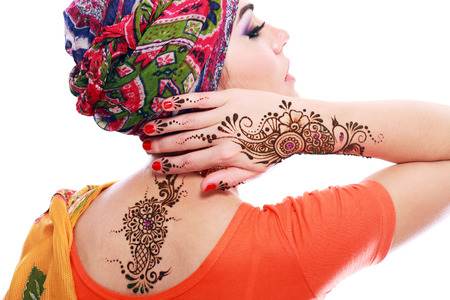 Beautiful woman arabian make up and turban on head with detail of henna being applied to hand and backt isolated  photo
