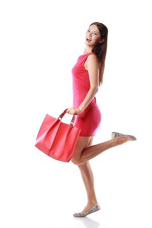 gelukkige winkelen jonge vrouw die wacht rode rug of tas - geïsoleerd op een witte achtergrond, full body, Aziatische model Stockfoto