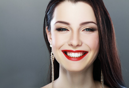 smile face: Close-up portrait of sexy caucasian young model with glamour red lips make-up. Perfect clean skin. Ukrainian woman purity face with bright lips makeup