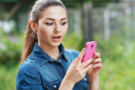 social behaviour: anxcios young girl looking at phone seeing bad news or photos there with disgusting emotion on her face