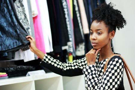 Compra da menina bonita africano jovem no departamento de vestir Imagens