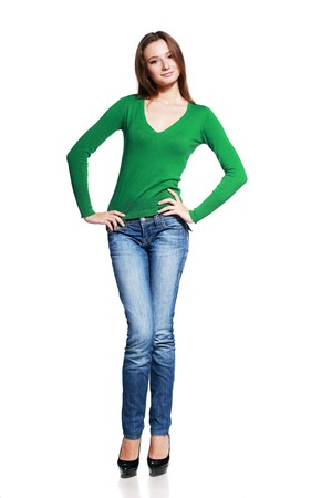 full  body: Full body young brunette woman in blue jeans posing on white background