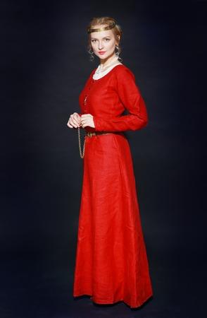 vestido medieval: Muy hermosa mujer de vestido rojo medieval en el estudio parece un paynting antaño se ve como una reina