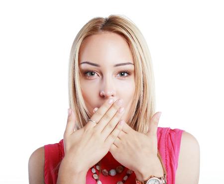femme bouche ouverte: Close-up portrait de surprise belle fille ferma la bouche avec les mains dans la stupéfaction. Sur fond blanc.