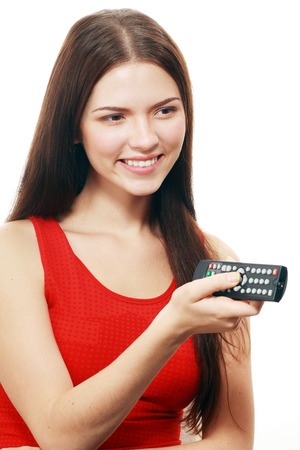 Happy woman holding TV remote control, over white background photo
