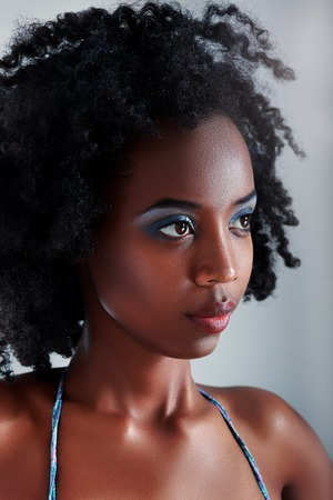 brown hair blue eyes: Beautiful african young woman looking outside the picture.