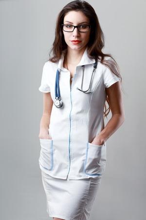 female doctor posing on light grey background