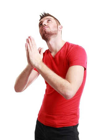 solicit: portrait of young man gesturing with clasped hands, pretty please with sugar on top, isolated on white background. Positive emotion facial expression feelings, signs symbols, body language.