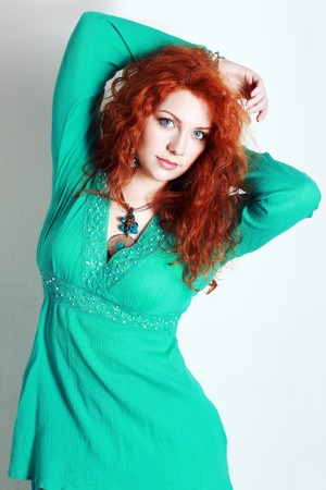 portrait of a beautiful woman with red curly hair. wearing a romantic green or turquoise dress