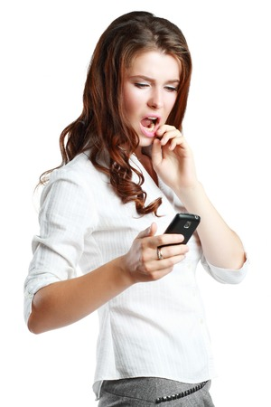dismayed: Young woman dismayed at something she sees on her cell phone