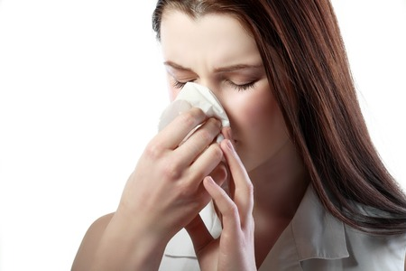 enfermos: Mujer joven enferma que sopla su nariz aisladas sobre fondo blanco Foto de archivo