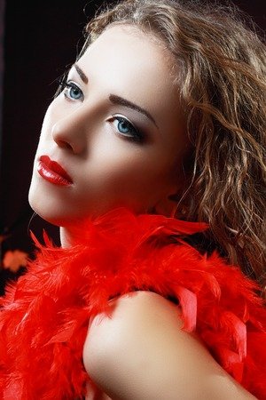 feather boa: Portrait of a Beautiful Hot Girl With Long Curly Hair with red feather boa Stock Photo