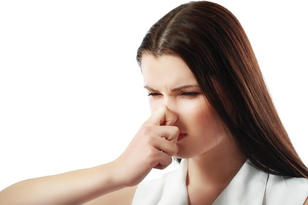 pinches: Closeup portrait young woman, disgust on face, pinches nose looks funny, something stinks, very bad smell, situation, isolated white background. Negative emotion, facial expression, feeling reaction