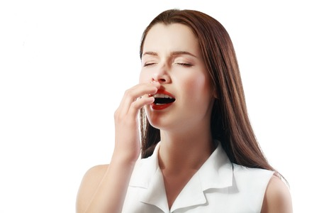 sickly: Sneezing young attractive woman close up isolated over white background