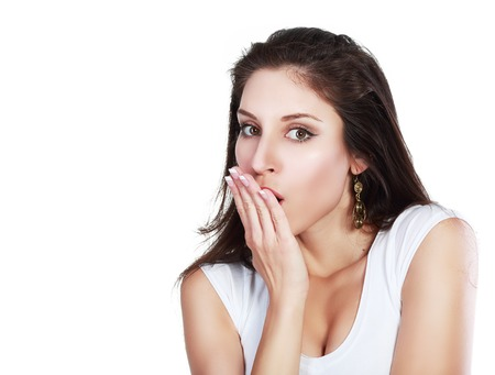 disbelief: A shocked and frightened woman covering her mouth in surprise and disbelief. Isolated on white. Stock Photo