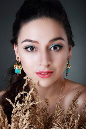 A beauty shot of a pretty young woman wearing an earrings in front of a dark background.