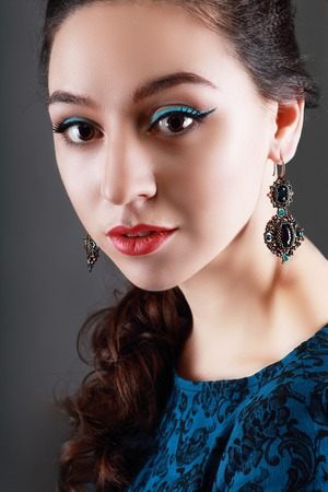 earing: A beauty shot of a pretty young woman wearing butterfly earrings in front of a dark background.