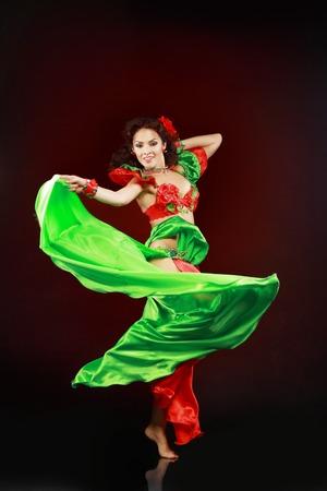 Un portrait d'une belle danseuse du ventre sur fond sombre