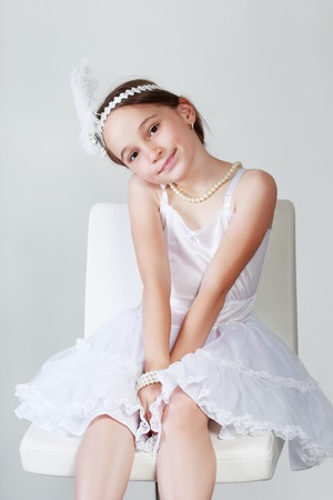 seductress: Portrait of cute little girl in luxurious dress and headbundle with feathers. Fashion photo