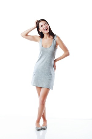 Thinking woman standing in full length isolated on white background in grey neutral dress. Mixed asian  caucasian young woman.