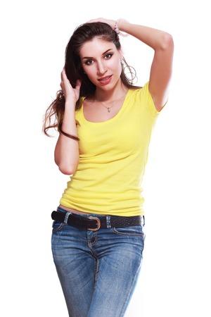 yellow shirt: beautiful woman posing over white background yellow shirt jeans Stock Photo