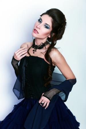 jabot: beautiful fashion vampire victorian style woman posing near wall fashion toning