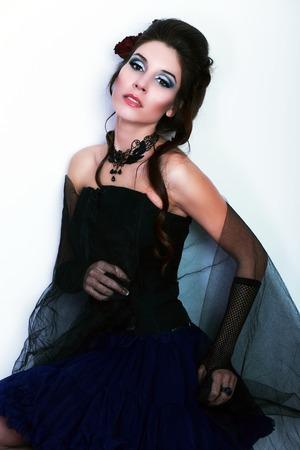 jabot: beautiful fashion vampire victorian style woman posing near white wall