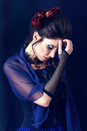 red hat: beautiful fashion vampire victorian style woman posing over dark background Stock Photo