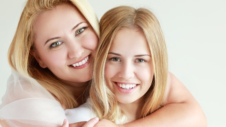 grown ups: Close up portrait of a mother and teen daughter being close and hugging at home being happy and joyful