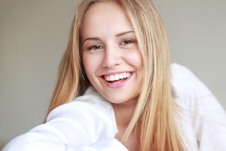ragazze bionde: headshot di bella ragazza teenager sorridente con grande sorriso a trentadue denti
