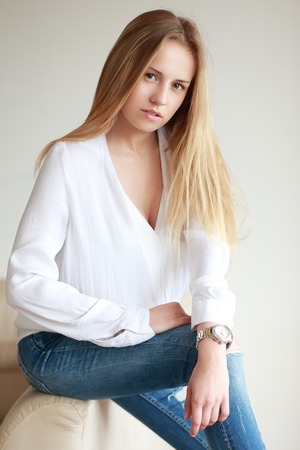 formal portrait: Teenage girl sitting in white shirt and blue jeans formal portrait