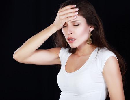 dolor de cabeza: Mujer que sufre de dolor de cabeza o el estrés sobre el backround negro