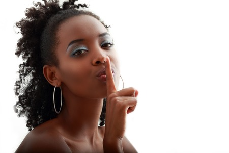 afro hairdo: Beautiful African American woman with a large afro hairdo making a hushing gesture holding her finger to her lips as she requests silence, with copyspace Stock Photo