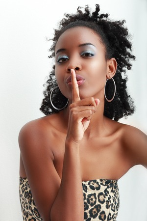 afro hairdo: Beautiful African American woman with a large afro hairdo making a hushing gesture holding her finger to her lips as she requests silence
