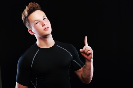 bronzed: young sporty man points a finger on a black background