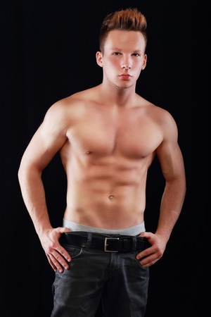 nude male body: sporty muscular young man in jeans posing over dark background. Stock Photo
