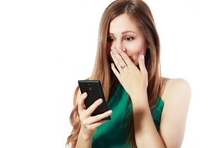 jolt: Closeup portrait, upset young woman, shocked, scared, surprised, by what she sees on cell phone, bad news, isolated white background. Negative human emotions, facial expressions, feelings, reaction