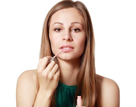 nariz roja: Pretty young woman applying liquid glossy lipstick Foto de archivo
