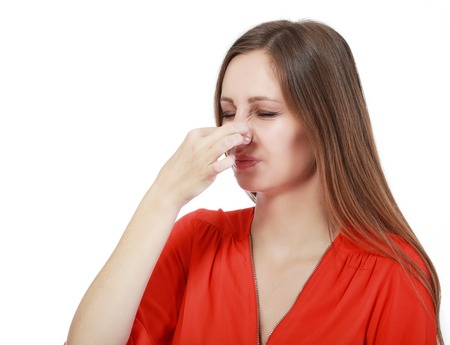 hyperhidrosis: Portrait of a young woman holding her nose because of a bad smell