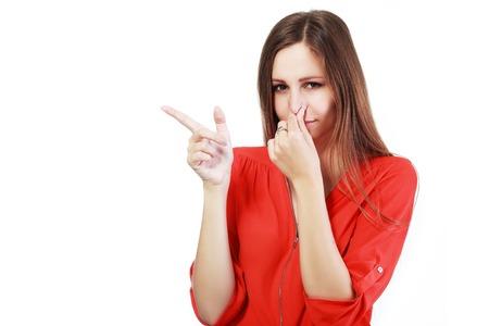 nariz: Retrato de una mujer joven sosteniendo su nariz debido a un mal olor