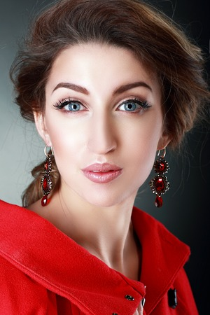 Portrait of Beautiful woman in Red Coat and Red Earrings. Luxury