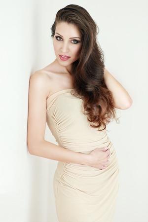capelli lunghissimi: Elegante ritratto della giovane e bella ragazza alla moda in studio in posa contro un muro bianco