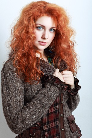 ropa de invierno: retrato de una mujer hermosa con el pelo rizado rojo en la ropa de invierno de punto Foto de archivo