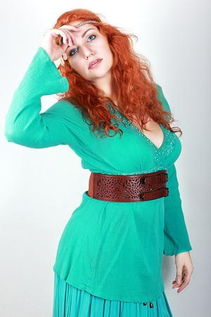 big girl: portrait of a beautiful woman with red curly hair wearing a green or turquoise dress. Stock Photo