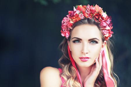 florecitas: hermosa hada: imagen filtrada de la morena linda chica en la corona de flores de loto y el maquillaje de color rosa posando con gracia en verde al aire libre copia espacio de fondo Foto de archivo