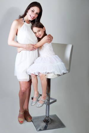 outfits: mother and daughter in same outfits posing on studio hugging