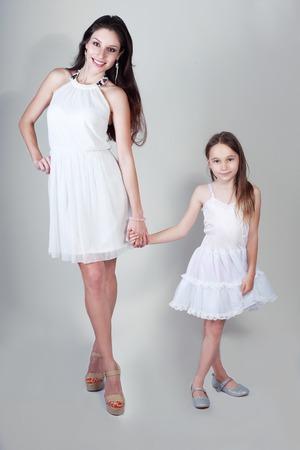 pessoas: mãe e filha em mesmas roupas que levantam no estúdio beijando