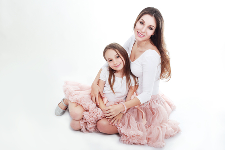 mother and daughter in same outfits posing on studio hugging