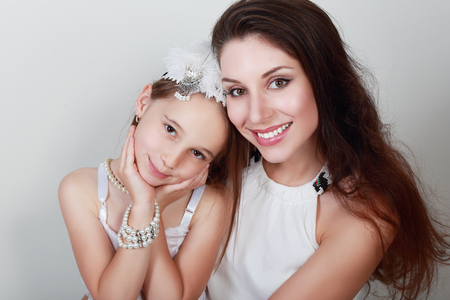 pretty little girl: mother and daughter in same outfits posing on studio hugging